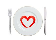 White plate with paint red heart symbol, spoon and fork isolated Royalty Free Stock Images