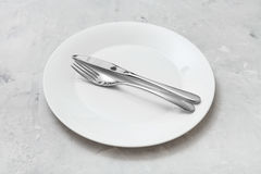 White plate with parallel knife, spoon on concrete Royalty Free Stock Photography