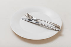 White plate with parallel knife, spoon on white Stock Photos