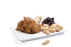White plate with peanut products. Like peeled peanuts, peanut butter, peanuts in chocolate and an unpeeled peanut Stock Photo