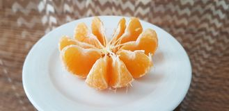 A white plate with peeled mandarin slices stand on glass table royalty free stock photos