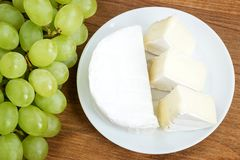 White plate with pieces of tasty cheese camembert and sweet green grapes on a brown wooden cutting board. Soft cheese covered with. Edible white mold. Top view royalty free stock image