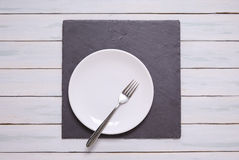 White plate place setting. White plate on a wooden background Stock Images