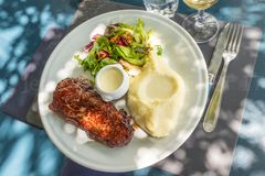 White plate of a pork chop with mashed potatoes meal, luxury atmosphere diner. White plate of a pork chop with mashed potatoes meal royalty free stock photos