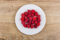 White plate with raspberries on wooden table. Top view Royalty Free Stock Image