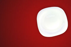 White plate on red background. Stock Images