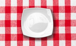 White plate on red checked fabric tablecloth Royalty Free Stock Photography