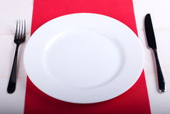 White plate on a red napkin Royalty Free Stock Images