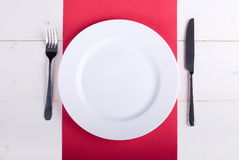 White plate on a red napkin Stock Photo