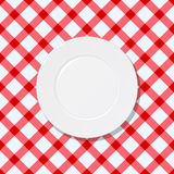 White plate on red and white checked tablecloth Royalty Free Stock Photography