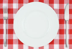 White plate on red and white checkered cloth. White plate with knife and fork on red and white checkered cloth Stock Photos