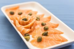 White plate with salmon sashimi and capers on blue background royalty free stock image
