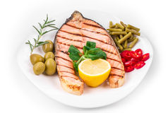 White plate of salmon steak with vegetables. Stock Image