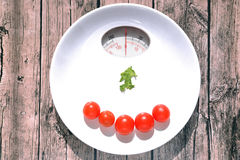 White plate with scales weight indicator. White plate with cherry tomatoes on it with scales weight indicator showing zero on wooden background Stock Photography