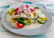 White plate serving of healthy Bananna, Strawberries, Avocado with Cream sitting on table. With blue grey and white table cloth stock image