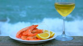 Wine and shrimp on a background of storm surf wave stock video footage