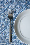White plate and silver fork. A white plate and silver fork on blue texture Royalty Free Stock Photos