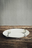 White Plate and silver  fork , knife. on wooden tabletop Stock Image