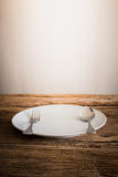 White Plate and silver  fork , knife. on wooden tabletop Royalty Free Stock Photos