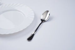 A white plate with silver fork and spoon isolated on white background with copy space. Dinner place setting. Table Setting. Stock Photos