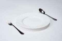 A white plate with silver fork and spoon isolated on white background with copy space. Dinner place setting. Table Setting. Stock Image