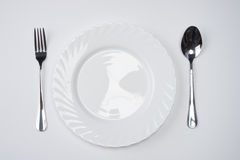 A white plate with silver fork and spoon isolated on white background with copy space. Dinner place setting. Table Setting. Stock Photo