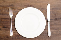 White plate with silver knife and fork Royalty Free Stock Image