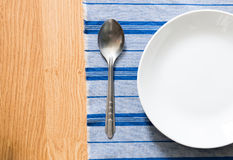 White plate and silver spoon Stock Image