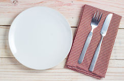 White plate and silverware on table Stock Photos