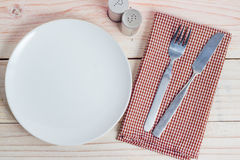 White plate and silverware on table Stock Images