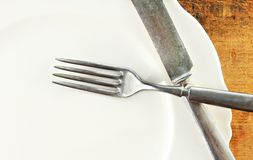 White Plate and Silverware Wooden Table Royalty Free Stock Image
