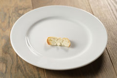 White plate with single dry slice of baguette bread Royalty Free Stock Photos