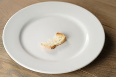 White plate with single dry slice of baguette bread Royalty Free Stock Photo