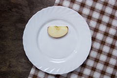 White plate with a slice of apple Royalty Free Stock Photography