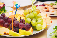 On a white plate sliced apples and grapes. Royalty Free Stock Photography