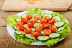 On a white plate are sliced cucumbers, tomatoes and lettuce leaves. Front view, close-up Royalty Free Stock Photography