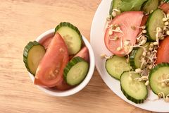 White plate. Slices of tomato and cucumber. Sprouted beans. Fresh salad.  stock photo