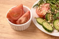 White plate. Slices of tomato. Sprouted beans. Fresh salad. Brown background stock photo