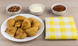 White plate with small pasties, bowls with sauce, spices Stock Photography