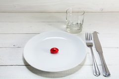 White plate with a small red easter egg,  knife, fork and drinki Stock Images