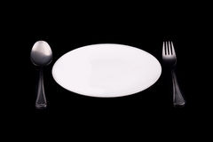 White plate with spoon and fork royalty free stock photography