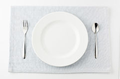 White plate spoon and fork. Plates and forks and spoons Stock Photos