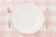 White plate spoon and fork. Plates and forks and spoons Royalty Free Stock Photo