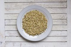 White plate with sprouted buckwheat. Inside on white-painted wooden table. Top view. Organic raw hulled groats. Close up background with copy space. Concept of royalty free stock image