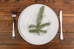 White plate with spruce branch, knife and fork on a brown wooden surface. A white plate with a spruce branch, a knife and a fork on a brown wooden surface. Close Royalty Free Stock Images