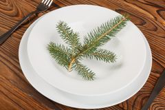 White plate with spruce branch, knife and fork on a brown wooden surface. A white plate with a spruce branch, a knife and a fork on a brown wooden surface. Close Stock Photo
