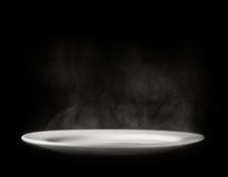 White plate with steam on black background. Photo of white plate with steam on black background royalty free stock photos
