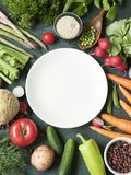 A white plate surrounded by vareity of fresh raw vegetables on r Royalty Free Stock Images