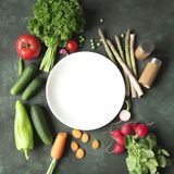 A white plate surrounded by fresh raw vegetables on rustic dark Stock Images
