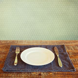 White plate on tablecloth over vintage background Royalty Free Stock Photos